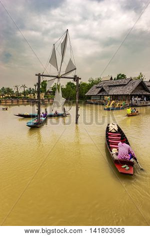 A man traveling by canoe in the river. The color of the water looks yellow and dirty. There are handmade wind vane and the windmill. There are houses built by traditional architecture where trees are.