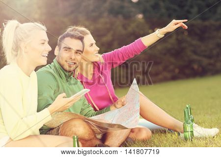 Picture of group of friends camping in forest and looking at map with phone
