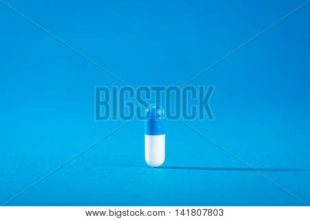 Close up medical capsule on the blue background