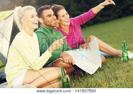 Picture of group of friends camping in forest and looking at map