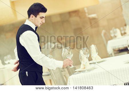 waiter man serving banquet table at restaurant