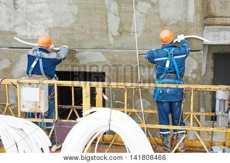 Facade plasterers sealing joint of building wall with putty mastic