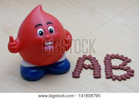 Ferrous Fumarate 200 mg with Vitamins for blood donor type AB after donating blood on wood background. poster