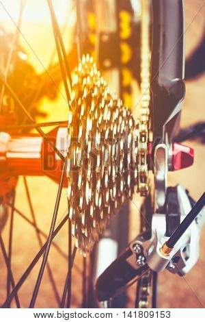 Closeup gear mountain bike wheel detail disc brake and rear derailleur with bright sunlight. Outdoor at the day time.