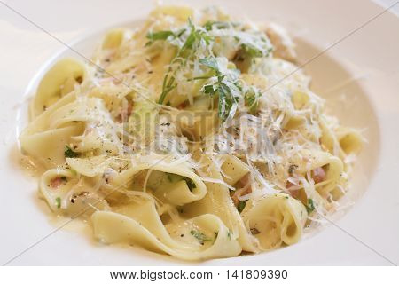 Tagliatelle pasta with cheese sauce, bacon, parsley and Parmesan