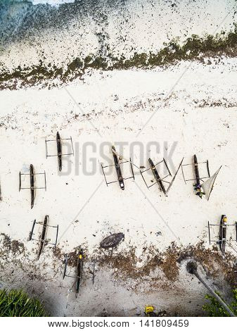 many wooden fishing boats on african seashore, top view, aerial photo