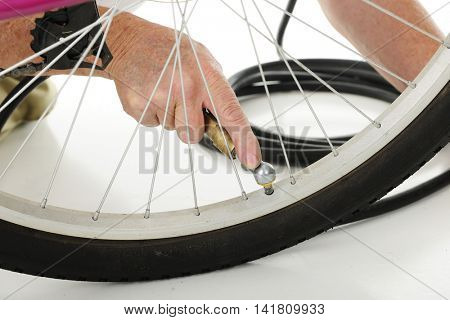 Close-up of an older man's hand filling a bicycle tire with air.  On a white background.