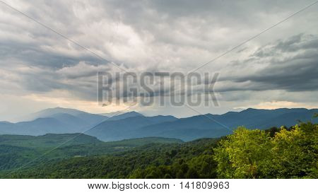 Bright grey sky with thunderclouds on sunset sloping green slopes of mountains and mountain valley.