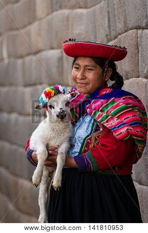 Native Peruvian Holding A Baby Lamb