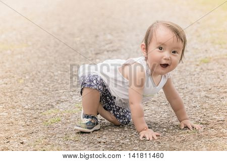 A baby girl crawls around in park with warm filter, are a normal part of a child's development.