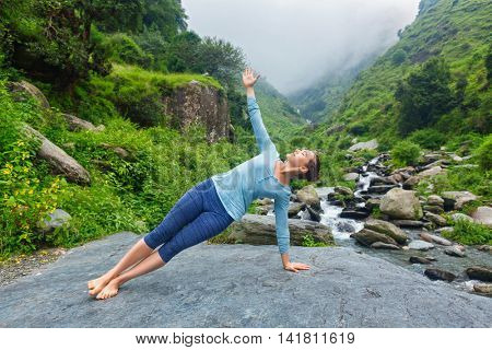 Yoga outdoors - beautiful sporty fit woman doing yoga asana Vasisthasana - side plank pose at tropical waterfall