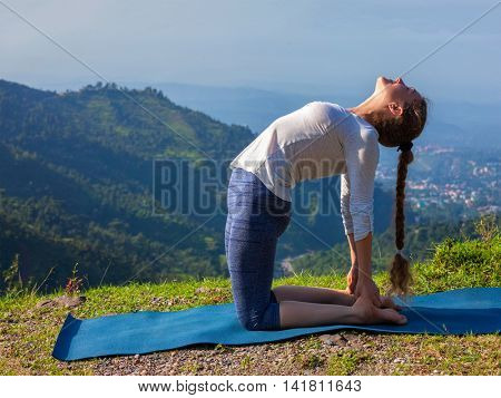 Yoga - outdoors  young beautiful slender woman yoga instructor doing camel pose Ustrasana asana exercise outdoors in mountains in the morning