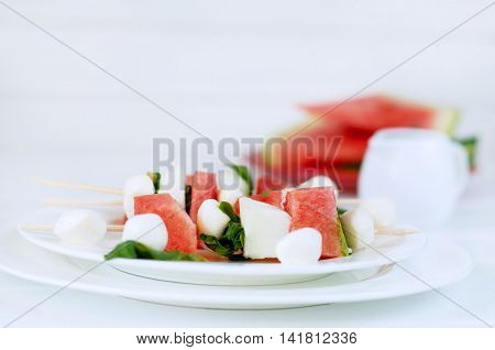 Watermelon kebab with spicy sauce basil and mozzarella cheese. Refreshing summer barbecue snack.