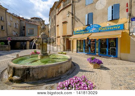 VALENSOLE, FRANCE - JULY 4. 2016: Central square with fountain and private shops at day time