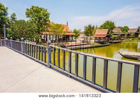 the bridge beside water with beautiful Thai house with tree, river and blue sky background, selective focus