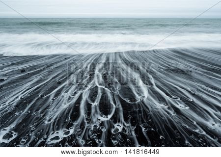 Ocean shore with black volcanic sand. Beautiful foam line and waves. Cloudy day . Beach near the village Vik, southern coast of Iceland, Europe