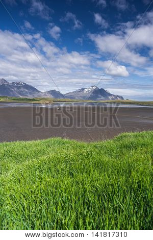 Summer landscape with green grass and beautiful sky on a sunny day. Swamp at the bottom of the Bay. View of Cape Stokksnes, southeastern coast of Iceland, Europe