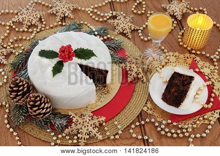 Christmas cake and slice, with egg nog, holly berries, candles, gold bauble snowflake decorations with bead strands over oak table background.