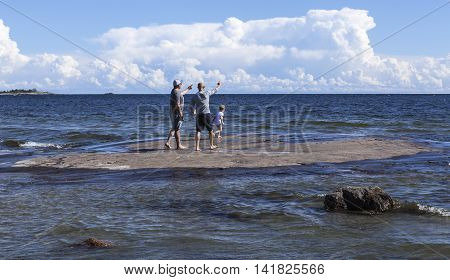 BALTIC SEA, SWEDEN ON AUGUST 03. Unidentified people on a rock on August 03, 2016 by the Baltic Sea, Sweden. Sea, clouds and thunderstorms in the background. Editorial use.