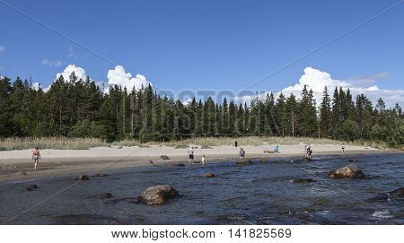 BALTIC SEA, SWEDEN ON AUGUST 03. Unidentified people on the beach on August 03, 2016 by the Baltic Sea, Sweden. Beach, forest and thunderstorm in the background. Editorial use.