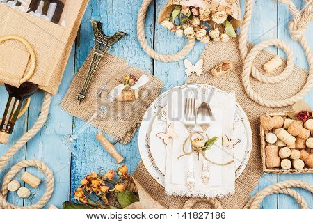 Tableware and silverware with dry flowers and different decorations on the blue old wooden background