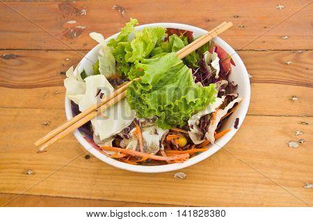 chopsticks wood on fresh salad on wood table