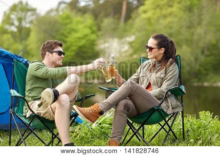 camping, travel, tourism, hike and people concept - happy couple clinking beer bottles at campsite tent