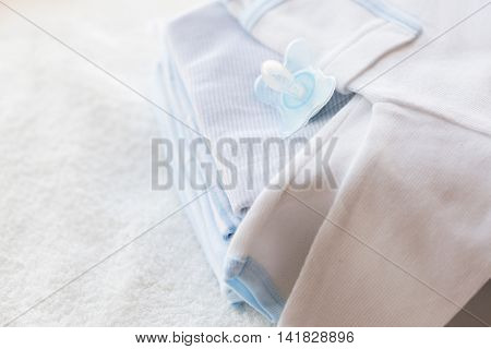 clothing, babyhood, motherhood and object concept - close up of baby soother and pile of clothes for newborn boy
