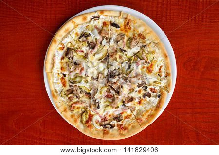 large pizza with meat cheese mushrooms on a white plate