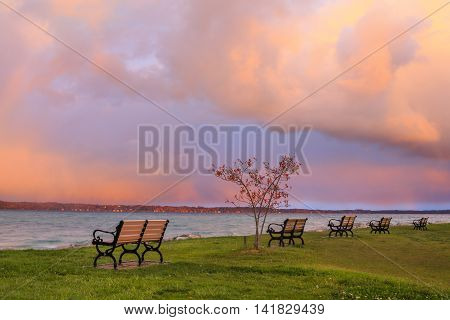 Benches and colorful storm clouds over Traverse Bay in early morning at Elk Rapids Michigan USA