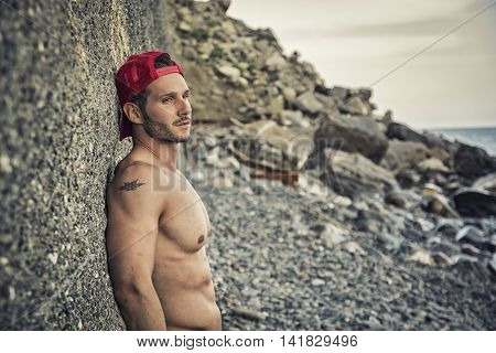 Handsome muscular shirtless man on the beach leaning on rock, looking away at the sea