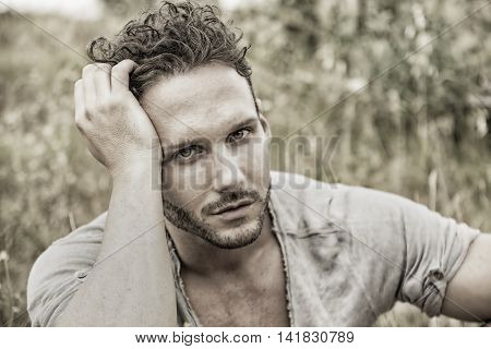 Good looking male model sitting on grass in a field, looking at camera