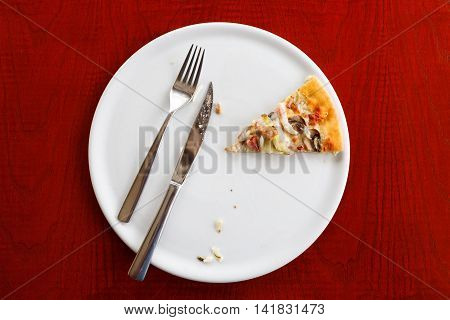 last piece of pizza on a white plate. Wooden table knife and fork