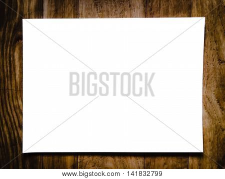 Blank white paper on blurred of wooden background and black vignette border
