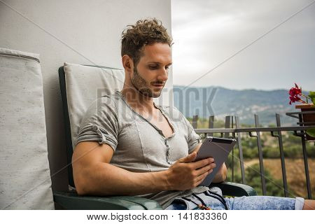 Handsome trendy man wearing t-shirt sitting and working, looking down at a tablet computer that he is holding, outdoor on house terrace