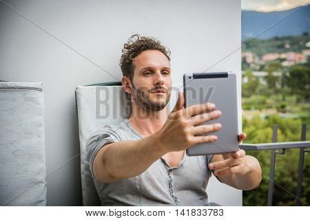 Handsome trendy man wearing t-shirt sitting and doing videochat, looking down at a tablet computer that he is holding, outdoor on house terrace