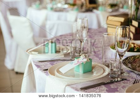 Table served with cutlery. on a plate and gift guest nameplate.