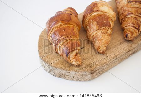 Breakfast with delicious croissant on wooden background.
