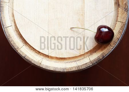 Farm concept. One cherry fruits in a row on top of oak barrel
