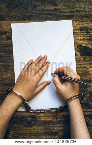 Female hands cuffed signing confession top view of police investigator detective desk poster