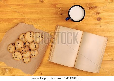 Homemade chocolate chip cookies milk cup and open book on rustic wooden table top view