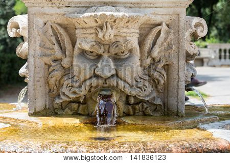 ROME ITALY - JUNE 14 2015: Marble fountain in the shape of the head of a man in the gardens of Villa Borghese Rome Italy.