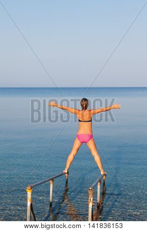 Young woman standing on the fence at the sea with arms raised up