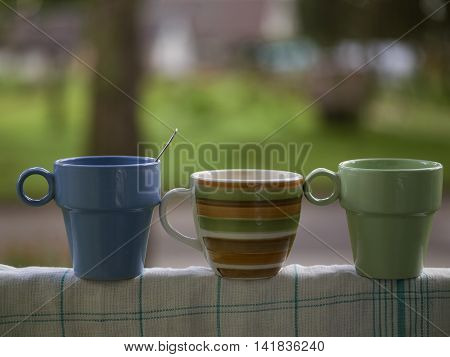 Three tea mugs standing in a row on a clean kitchen towel front shot with a blurred background