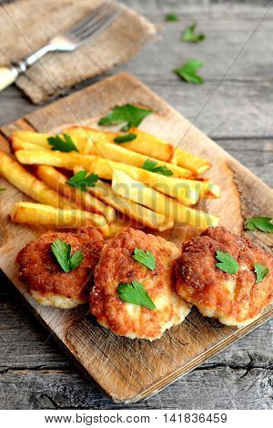 Fried cutlets cooked with Turkey mince. Fried potatoes. Turkey meat patties served with potatoes and garnished with parsley on a wooden board. Rustic stile. Closeup