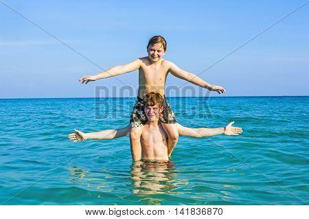 Boys Having Fun Playing Piggyback In The Warm Ocean