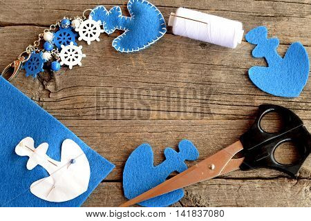 Felt anchor keychain with beads and wooden ship wheel, scissors, thread, pin, blue felt piece on wooden background with empty place for text. Needlework and sewing concept. Summer kids activity
