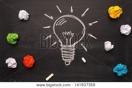 Crumpled paper on a blackboard with a handdrawn lightbulb new idea concept background