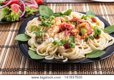 Closeup Black Plate With Spaghetti And Pieces Of Stewed Chicken