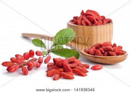 berberries near goji berries heap and wooden spoon bowl with goji isolated on white background